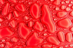 小滴在红色,表面无光泽的背景的水阐明与精美光 免版税库存照片