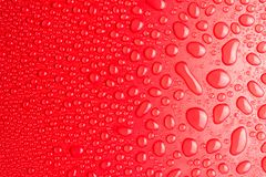 小滴在红色,表面无光泽的背景的水阐明与精美光 库存图片