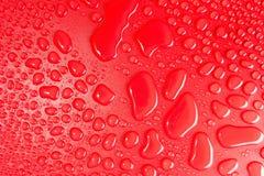小滴在红色,表面无光泽的背景的水阐明与精美光 免版税图库摄影