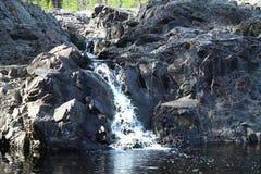 小瀑布在卡累利阿在有岩石的森林里 免版税库存图片
