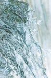 水小瀑布瀑布放出飞溅背景,大详细的垂直的特写镜头,明亮的蓝色,海绿色淡色 库存照片