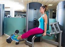 小牛健身房锻炼机器的引伸妇女 免版税图库摄影