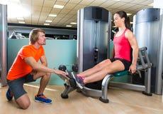 小牛健身房锻炼机器的引伸妇女 免版税库存图片