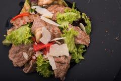 小牛肉、乳酪和红辣椒沙拉在黑色的盘子 库存照片