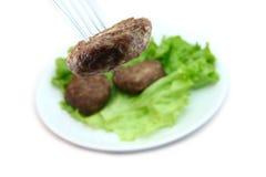 小牛肉炸肉排用在白色背景的莴苣 免版税库存照片