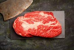 小牛肉牛排使玄武岩,肉的一把刀子有大理石花纹在黑暗的背景 免版税库存图片