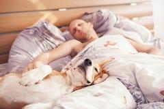 小猎犬与他的所有者的狗睡眠在床上 免版税库存图片