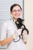 小猫亲吻兽医,当听时 免版税库存图片