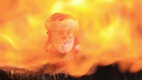 小玩具塑料圣诞老人熔化在火下强有力的热的火焰  慢的行动 股票视频