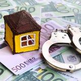 小玩具房子和手铐是在一套的谎言绿色金钱 库存照片