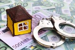 小玩具房子和手铐是在一套的谎言绿色金钱 免版税库存图片