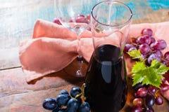 小玻璃水瓶用干红葡萄酒、两个酒杯和葡萄 图库摄影