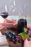 小玻璃水瓶用干红葡萄酒、两个酒杯和葡萄 免版税库存图片