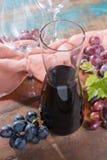 小玻璃水瓶用干红葡萄酒、两个酒杯和葡萄 库存照片