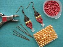 小珠、家具和工具为做耳环,手工制造首饰,宏观方式 库存图片