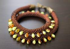 从小珠的不同的类型的被编织的项链木表面上的 库存图片