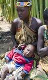 小珠装饰的画象妇女与Hadzabe部落的婴孩 图库摄影