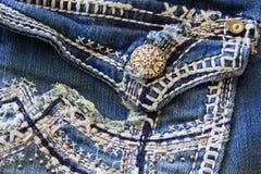 小珠铆钉和手缝的细节增加了到牛仔裤口袋 免版税库存图片