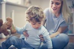 小男婴有与他的母亲的戏剧 在活动中 免版税图库摄影