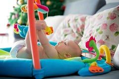 小男婴,在家使用与五颜六色的玩具 免版税库存图片