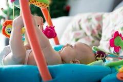 小男婴,在家使用与五颜六色的玩具 免版税库存照片