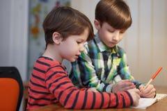 小男孩一起研究算术在书桌 免版税图库摄影