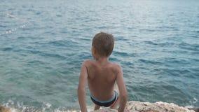 小男孩下降一个高岩石在亚得里亚海 达尔马提亚 克罗地亚 影视素材