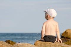 小男孩与他的回到岩石坐在游泳裤的海滨,蓝天,文本的空间 免版税库存照片