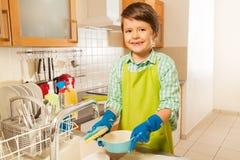 小男孩与拖把的洗涤盘在厨房水槽 库存照片