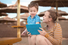 小男孩与是母亲在海滩胜地 免版税库存照片
