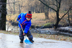 小男孩与锹的清洁冰 免版税库存图片