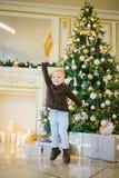 小男孩为喜悦跳在圣诞树旁边 免版税库存图片
