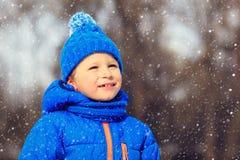 小男孩享用在冬天自然的第一雪 图库摄影