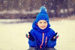 小男孩享用在冬天自然的第一雪 库存照片