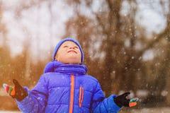 小男孩享用在冬天自然的第一雪 免版税库存照片