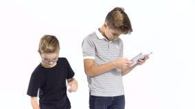 小男孩从更老的兄弟的手拿走片剂在白色背景 股票录像