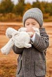 小男孩体贴亲吻他的与他的闭上的眼睛的玩具兔宝宝 免版税库存照片