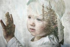 小男孩作白日梦,看窗口,两次曝光 免版税图库摄影