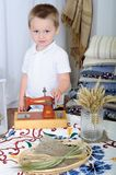 小男孩使用与机器桌面 有土气装饰的屋子 库存图片