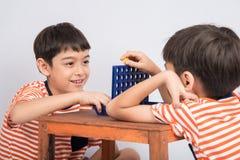 小男孩使用连接四场比赛软的焦点在目光接触室内活动 图库摄影