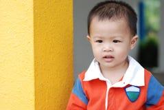 小男孩依靠柱子 免版税库存照片