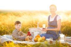 小男孩儿子和他怀孕的母亲一顿野餐的在一个美好的秋天或夏日 愉快的家庭和健康吃概念 库存照片