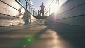 小男孩剪影在一个木桥骑通过妇女小提琴手的一辆自行车在日落 股票录像