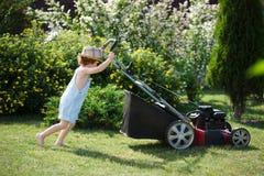 小男孩割有刈草机的草坪 免版税库存图片