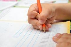 小男孩努力地写与铅笔在他的笔记本 免版税库存图片