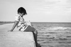 小男孩单独坐走道海上 库存图片
