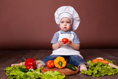 小男孩厨师红萝卜,胡椒,蕃茄,莴苣, 库存图片