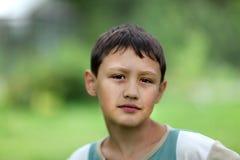 小男孩反对绿草的10岁 库存图片