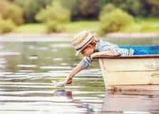 小男孩发射从老小船的纸船在湖 免版税图库摄影