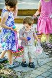 小男孩发现一个蓝色复活节彩蛋 免版税图库摄影